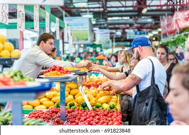 Montreal, Canada - May 28, 2017: People trying samples and buying produce by fruit and vegetable stands at Jean-Talon farmers market with coin change