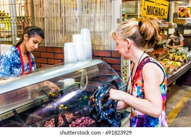 Montreal, Canada - May 28, 2017: Woman selling olives in Jean Talon market with people buying inside building in city in Quebec region