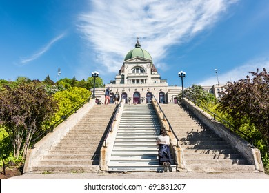 Montreal, Canada - May 28, 2017: St Joseph's Oratory on Mont Royal with woman praying on steps in Quebec region city