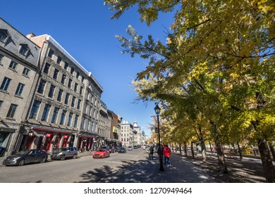 MONTREAL, CANADA - NOVEMBER 4, 2018: View of Old Montreal seafront, or Vieux Montreal, Quebec, in the autumn, with its yellow leaves trees and stone buildings on Rue de la Commune street