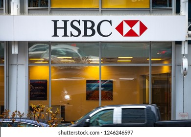 MONTREAL, CANADA - NOVEMBER 5, 2018: Logo of the HSBC Bank, on their main branch in Montreal with cars passing by. HSBC is a british bank spread worldwide