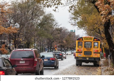 MONTREAL, CANADA - NOVEMBER 6, 2018: North American Yellow School Bus parked on a street, waiting for students with cars passing by with information in French, according to Quebec French speaking rule