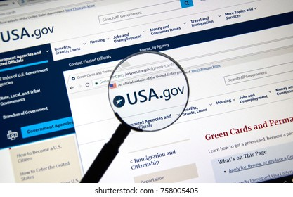 MONTREAL, CANADA - NOVEMBER 7, 2017: usa.gov website with green card regulations page under magnifying glass. The site is an official website of the United States government