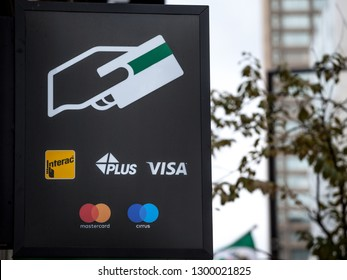 MONTREAL, CANADA - NOVEMBER 7, 2018: Sign on an ATM with the logos indicating the credit and debit pay cards accepted, that include Visa, mastercard, Cirrus, Plus, and the Canadian system Interac