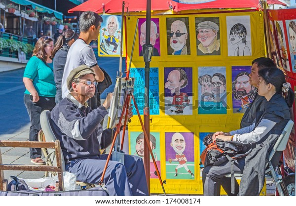MONTREAL, CANADA, OCTOBER 12, 2013 - artist painting caricatures and his clients in the street of Old Montreal