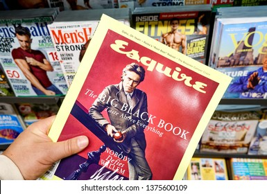 MONTREAL, CANADA - OCTOBER 9, 2018: Esquire magazine in a hand over a stack of magazines. Esquire is an American men's magazine, publishing by the Hearst Corporation