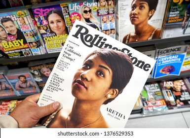 MONTREAL, CANADA - OCTOBER 9, 2018: Rolling Stone magazine in a hand over a stack of magazines with Aretha Franklin on the front cover. Rolling Stone is an American monthly magazine