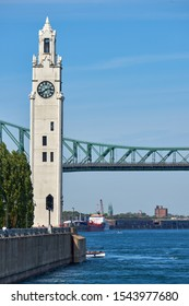 MONTREAL, CANADA - SEPTEMBER 13, 2019: Shot of the impressive Montreal's Jacques Bridge and a clock tower with an industrial zone visible behind the main scene