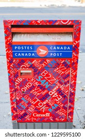 MONTREAL, CANADA - SEPTEMBER 16, 2018: A unique, red, bilingual Canada Post mailbox beside a road is decorated with a collage of red, white, and blue postal codes.