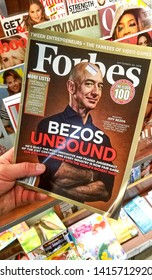 MONTREAL, CANADA - SEPTEMBER 28, 2018: Forbes magazine with Jeff Bezos on the cover in a hand. Jeff Bezos is president of Amazon. Forbes is an American family-controlled business magazine.