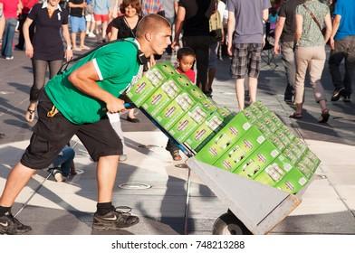 MONTREAL CITY - JUNE 29: Employee transporting several packs of Heineken beers on the street on June 29, 2013. Heineken is a very popular beer in Montreal.