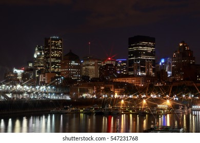 Montreal Downtown Panorama at night. Montreal reflected in water at dusk with city lights and urban buildings. Night city lights reflected in the water. Quay in the colorful bright lights with rays.