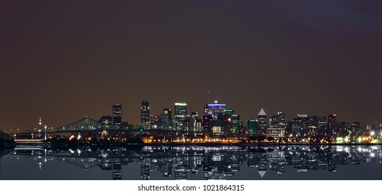 Montreal Downtown Panorama at sunset. Silhouettes of buildings reflected in the water at sunset. Montreal reflected on the river at dusk with city lights and urban buildings. Overcast sky.