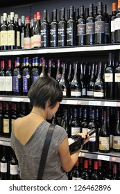 MONTREAL - JULY 8: An unidentified woman looks at a bottle of red wine in a Quebec Alcohol Corporation liquor store, on July 8, 2012 in Montreal, Quebec, Canada.