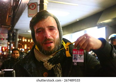 MONTREAL - MARCH 27: A journalist holds up his press pass after being pepper sprayed by police during a student protest in Montreal on March 27, 2015.