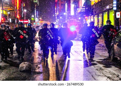 MONTREAL - MARCH 27: Police in heavy riot gear charge at a crowd of protesters during an anti-austerity demonstration on March 27, 2015 in Montreal, Quebec.