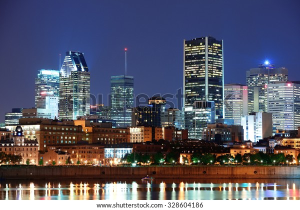 Montreal over river at dusk with city lights and urban buildings