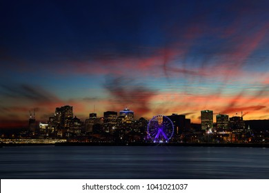 Montreal over river at sunset with city lights and beautiful urban buildings. Montreal Downtown Panorama at sunset. Beautiful clouds at sunset. Silhouettes of buildings at night. Montreal at night.