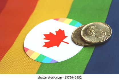 Montreal, QC / Canada - April 17 2019: one dollar Loonie coins, red maple leaf, gay rainbow flag.On 23 April comes commemorative Equality coin for 50 year decriminalization of homosexuality in Canada.