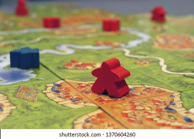 Montreal, QC / Canada - April 7 2019: a board game of Carcassonne played with blue and red meeples, a classic with cardboard tiles, inspired by ancient medieval French city with fortresses and plains.