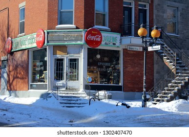 Montreal QC / Canada - February 1 2019: A winter street on the Plateau Mont Royal with an old convenience store and soda commercials, a lamppost and an outside staircase in front of a red brick house