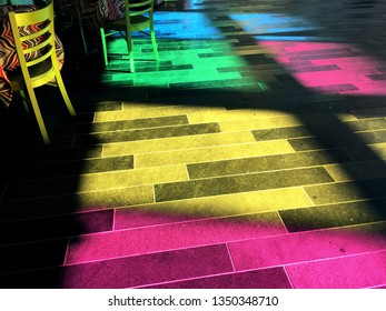 Montreal, QC / Canada - March 19 2019: colorful reflections from the colored glass windows in the Congress Palace (Palais des Congres) in Old Montreal, and the Trois Amigos restaurant chair.