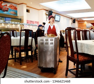 MONTREAL QC/CANADA FEBRUARY 12 2018 A chinese lady serving food from her dim sum trolley in the famous Restaurant Ruby Rouge in Montreal's chinatown