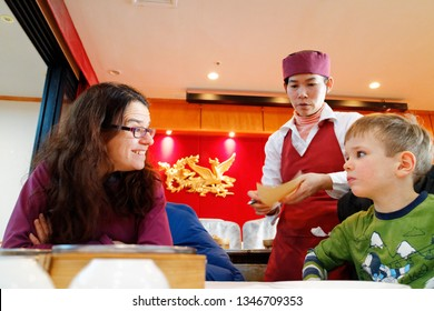MONTREAL QC/CANADA FEBRUARY 12 2018 A mother beaming at her five year old son as dim sum dishes are served in Ruby Rouge chinese restaurant in Montreal