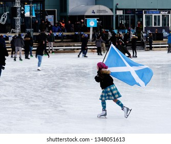 MONTREAL QC/CANADA JANUARY 20 2018 A skater in Montreal Old Port flying the Saltire, celebrating their Scottish ancestry in the annual Great Canadian Kilt Skate