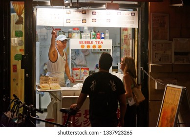 MONTREAL QC/CANADA JULY 20 2018 A chinese street food kiosk owner showing his menu to two customers in Montreal Chinatown on Rue de la Gauchetiere