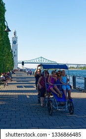 MONTREAL QC/CANADA JULY 21 2018 People rising a pedal quadricycle along Victoria Quay (Clock Tower Quay) in Montreal, Quebec