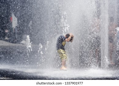 MONTREAL QC/CANADA JULY 21 2018 Children cooling off playing in water fountains in on Rue Jeanne Mance in Montreals Entertainment District. Taken during the 2108 heatwave.