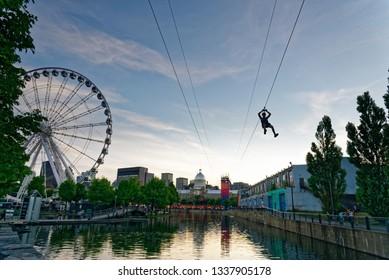 MONTREAL QC/CANADA JULY 21 2018 A person descending the zipline in Montreal Old Port with La Grande Roue de Montreal behind