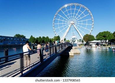 MONTREAL QC/CANADA JULY 21 2018 People crossing the bridge to Ïle Bonsecours in Montreal Old Port with the big wheel La Grande Roue behind
