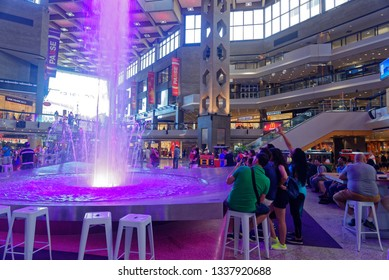 MONTREAL QC/CANADA JULY 21 2018 A group of young people taking photos of a large fountain in the Complexe Desjardins shopping centre in downtown Montreal