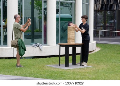 MONTREAL QC/CANADA JULY 22 2018 A man and his son playing giant Jenga outside at the Jeux Loto Quebec games festival in Montreal
