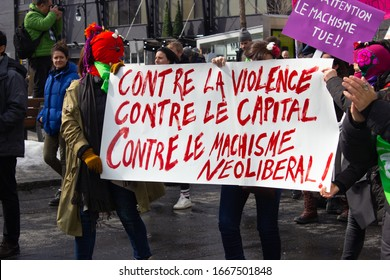 """Montreal, QC/Canada - March 8, 2020: Masked women holding sign """"Contre la Violence Contre le Capital Contre le Machisme Neoliberal!"""" during Woman Demonstration in Montreal on International Woman's Day"""