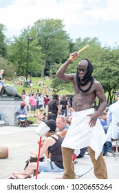 Montreal, Quebec, Canada - 2 July 2017: Black man beats on metal tin can, joins music produced in the famous drum circle Tam Tams at the base of Mont Royal in Parc du Mont Royal, Montreal, Canada.