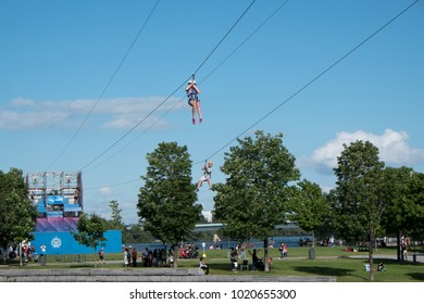 Montreal, Quebec, Canada - 2 July 2017: People riding the Tyrolienne MTL Zipline in Old Port Montreal along the pier of the St Lawrence River. People having a picnic in the grass on a summer day.