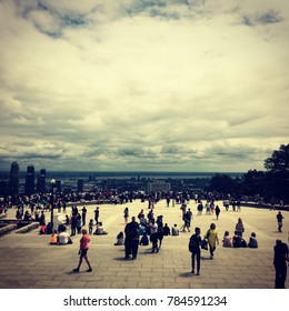 Montreal, Quebec, Canada - 2 July 2017: People walking around the summit overlook at the top of Mont Royal on a summer day. Cloudy day, view of Montreal skyline from Mont Royal, filter effect added.