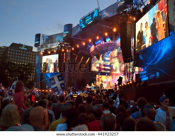 Montreal Quebec Canada 23 June 2016 Quebecers celebrate National St John the Baptist Day . Crowd waving flag cheering singers Eric Lapointe, Brigitte Boisjoli and musicians on stage in concert .