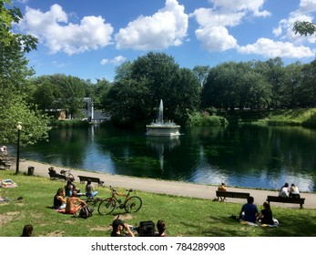 Montreal, Quebec, Canada - 3 July 2017: People relaxing and enjoying the sunshine at La Fontaine Park in Montreal. People sitting the lawn and benches around the small lake on the holiday weekend.