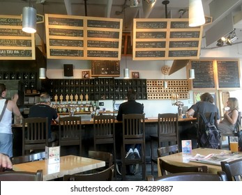 Montreal, Quebec, Canada - 4 July 2017: People sitting at the bar drinking beers at La Succursale a brewpub in Vieux Rosemont area of Montreal. Extensive beer list written in chalk behind the bar.