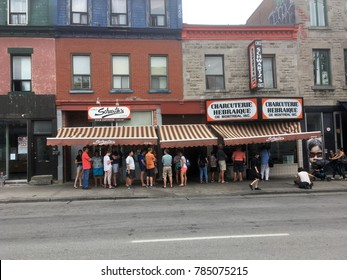 Montreal, Quebec, Canada - 7 July 2017: People queueing at lunchtime at Schwartz's Delicatessen, one of Montreal's oldest Jewish delis, claiming to serve the best smoke meats in Montreal since 1928.