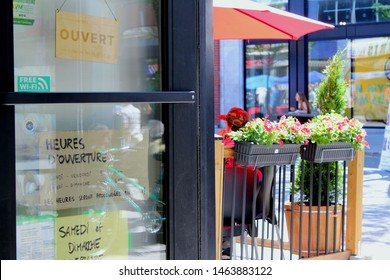 """Montreal, Quebec / Canada - 7 June 2019: entrance to cafe in city center on Plateau Mont Royal. Written on the door """"Open; opening hours; monday-friday, saturday-sunday, hours prolonged in July"""""""