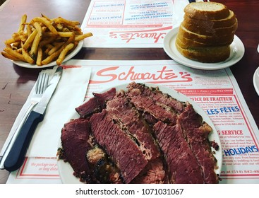 Montreal, Quebec, Canada: April 13, 2018: A large order of Schwartz's smoked meat on a white plate with a side dish of rye bread and french fries served at Schwartz's deli.