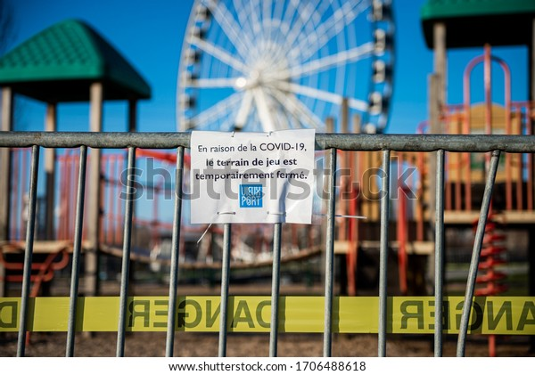 Montreal Quebec Canada April 17 2020: Playgrounds closed due to COVID-19 sign in Montreal's old port park is seen in background, french sign