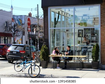 Montreal, Quebec / Canada - April 22 2019: people on a sunny spring day in a street cafe of Mile End hipster trendy neighborhood, enjoying the sun and talking to each other.