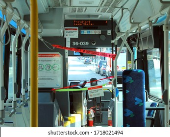 Montreal, Quebec / Canada - April 29 2020: a city bus interior with police tape for driver protection, danger of Covid-19 coronavirus contamination, social distancing during pandemic of a new virus.