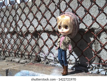 Montreal, Quebec / Canada - April 30 2019: a collectible Japanese doll Blythe is leaning against a rusty mesh fence on the Plateau Mont Royal, a hipster hangout neighborhood in the heart of the city.